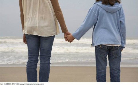 mother_and_daughter_9-11_holding_hands_on_beach_rear_view_tm_500033
