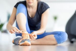 closeup-of-woman-tying-shoelace-on-gym-floor_1262-3504